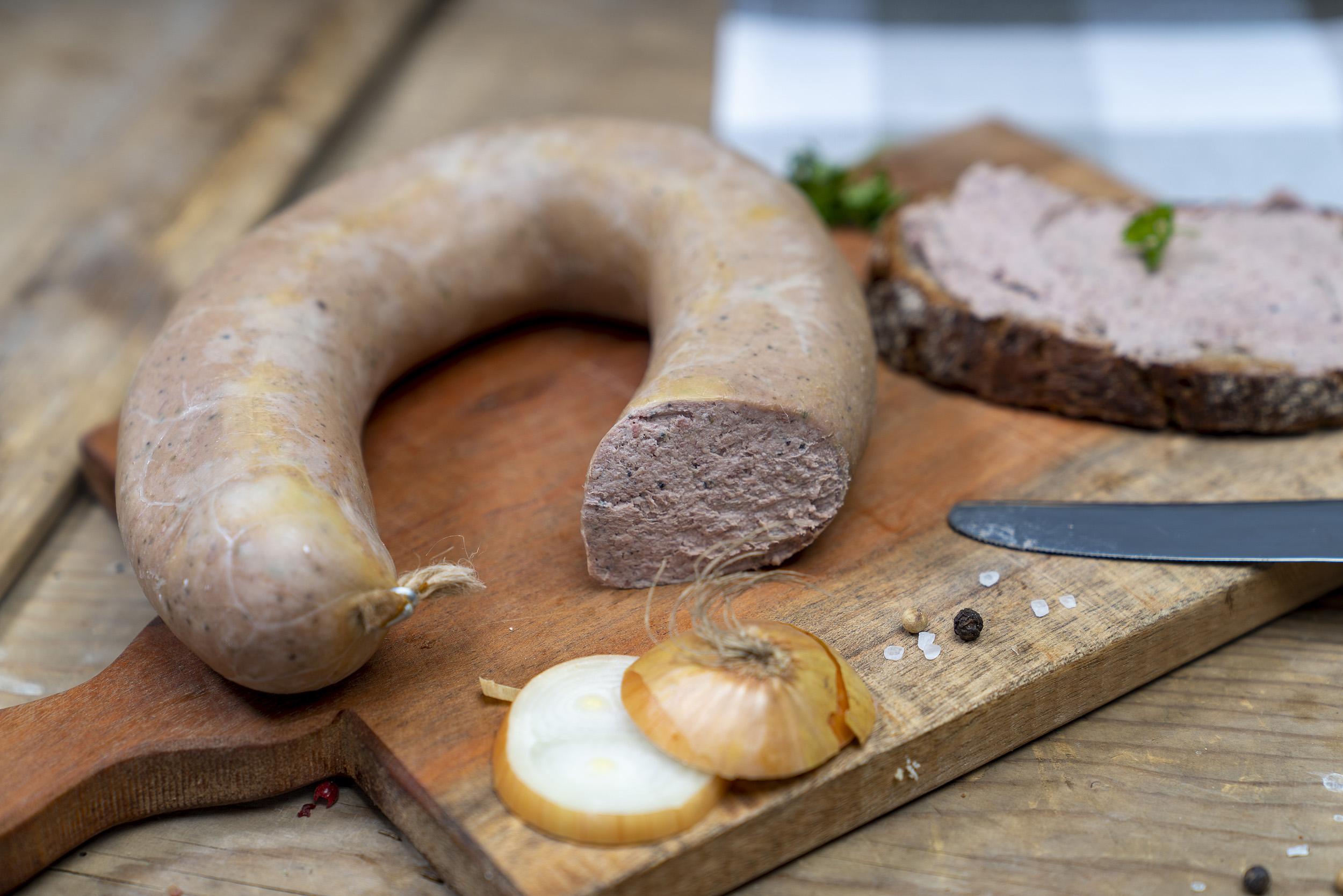 Auf einem Brett eine Leberwurst, ein geschmiertes Brot damit und Zwiebeln.