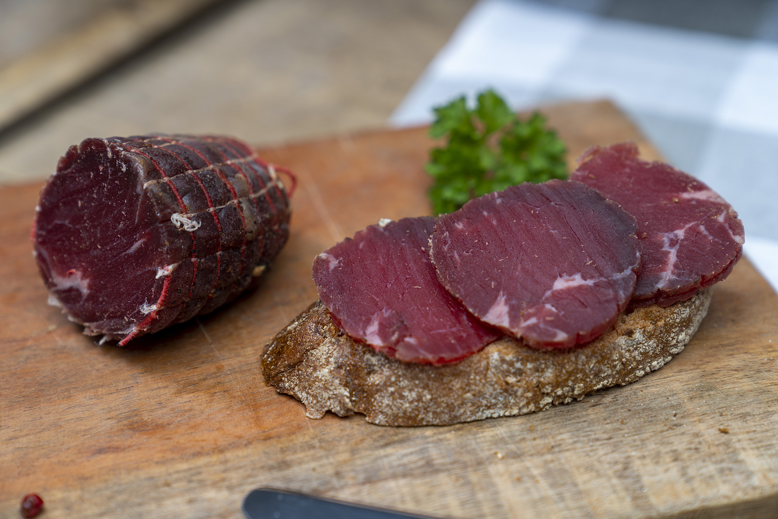 Ein Brot mit Rinderschinken. Auch auf dem Brett das Schinkenstück und Petersilie.