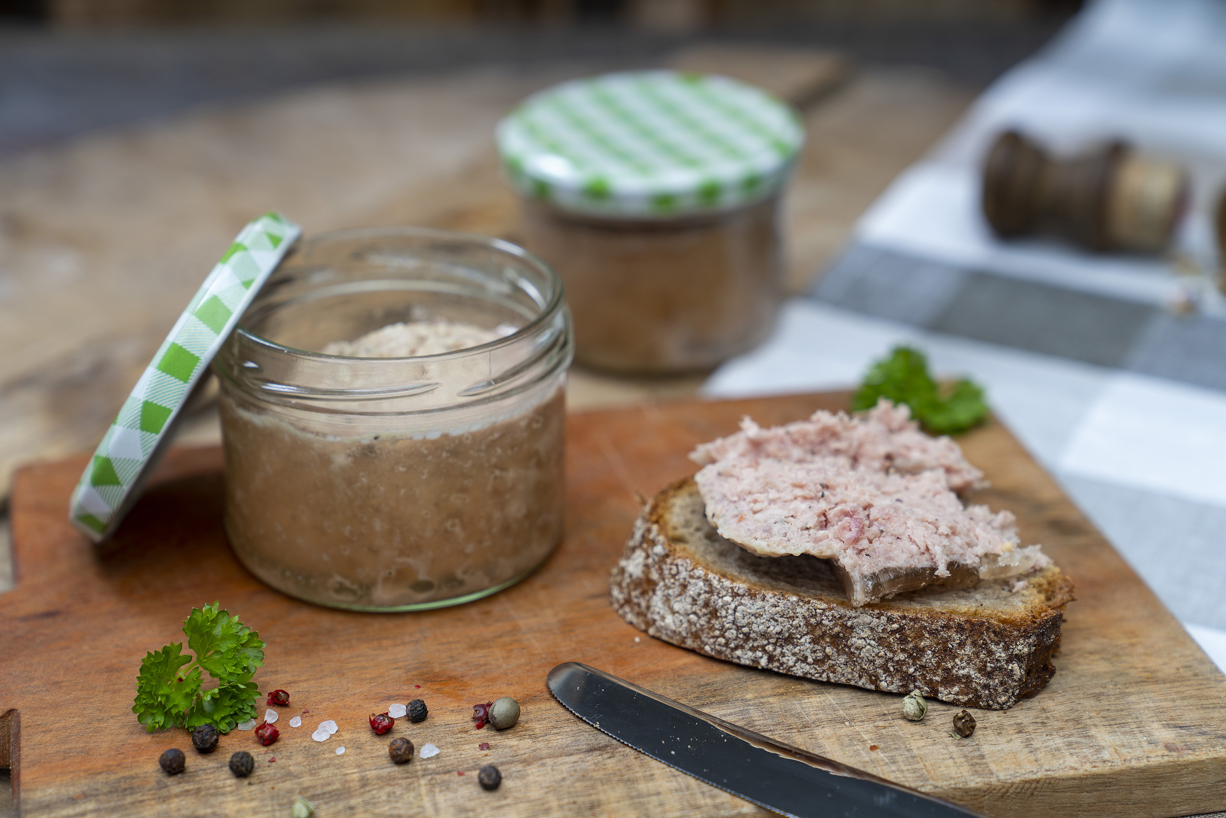 Auf einem Holzbrett steht ein Glas Schartenwurst. Daneben eine Scheibe Brot mit der Wurst. Drum herum Kräuter und Gewürze. Hinten ein weiteres Glas.