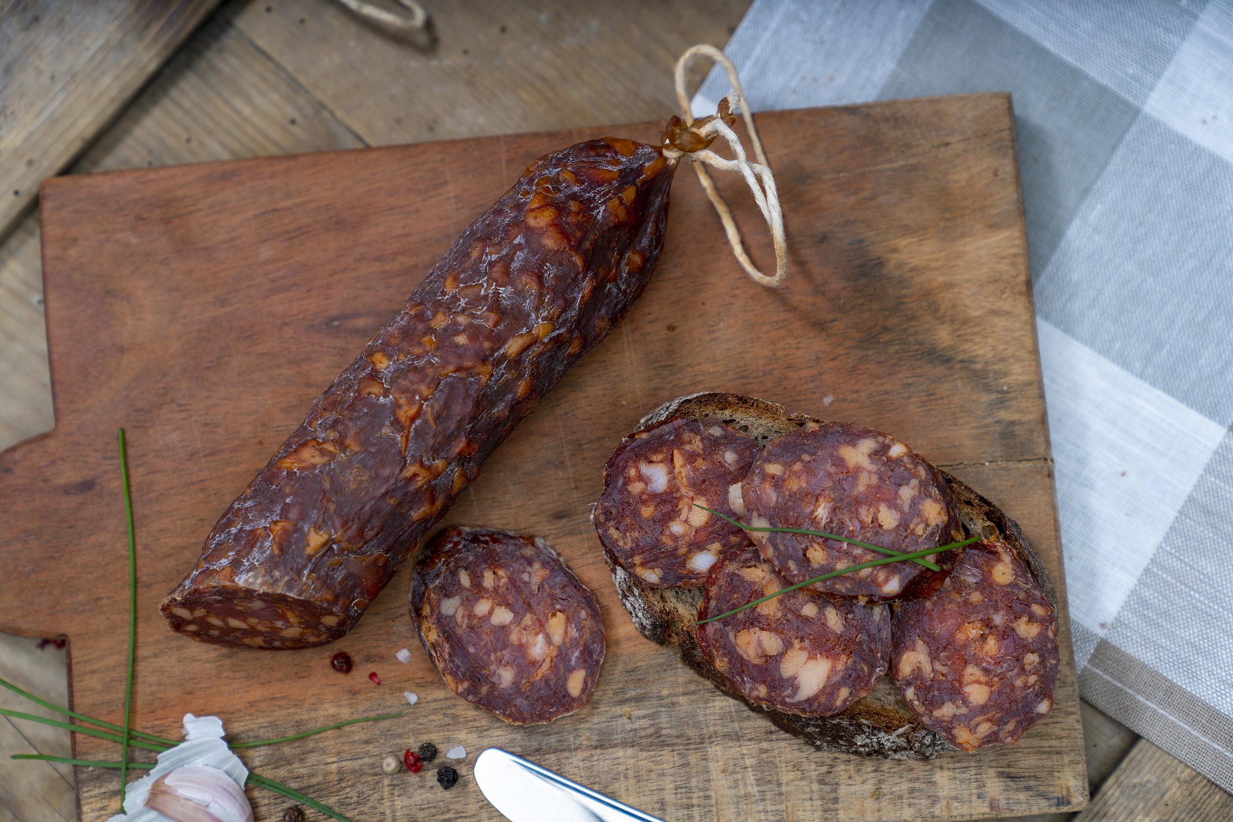 Angeschnittene Ungarische Salami auf einem Brett. Daneben eine Schnitte mit der Wurst und Gewürze.