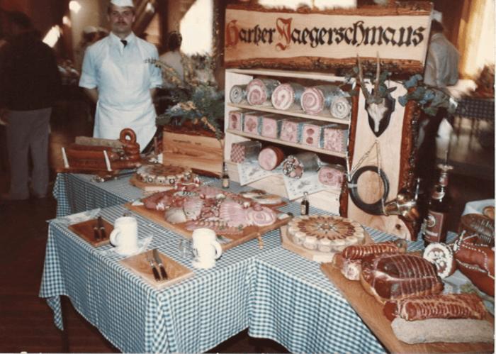 Ein großer Tisch mit verschiedenen Fleischprodukten. Sie sind alle Teil von Erwin Fessels Meisterstück. Auf dem Tisch ein Holzregal unter der Überschrift Harzer Jägerschmaus.