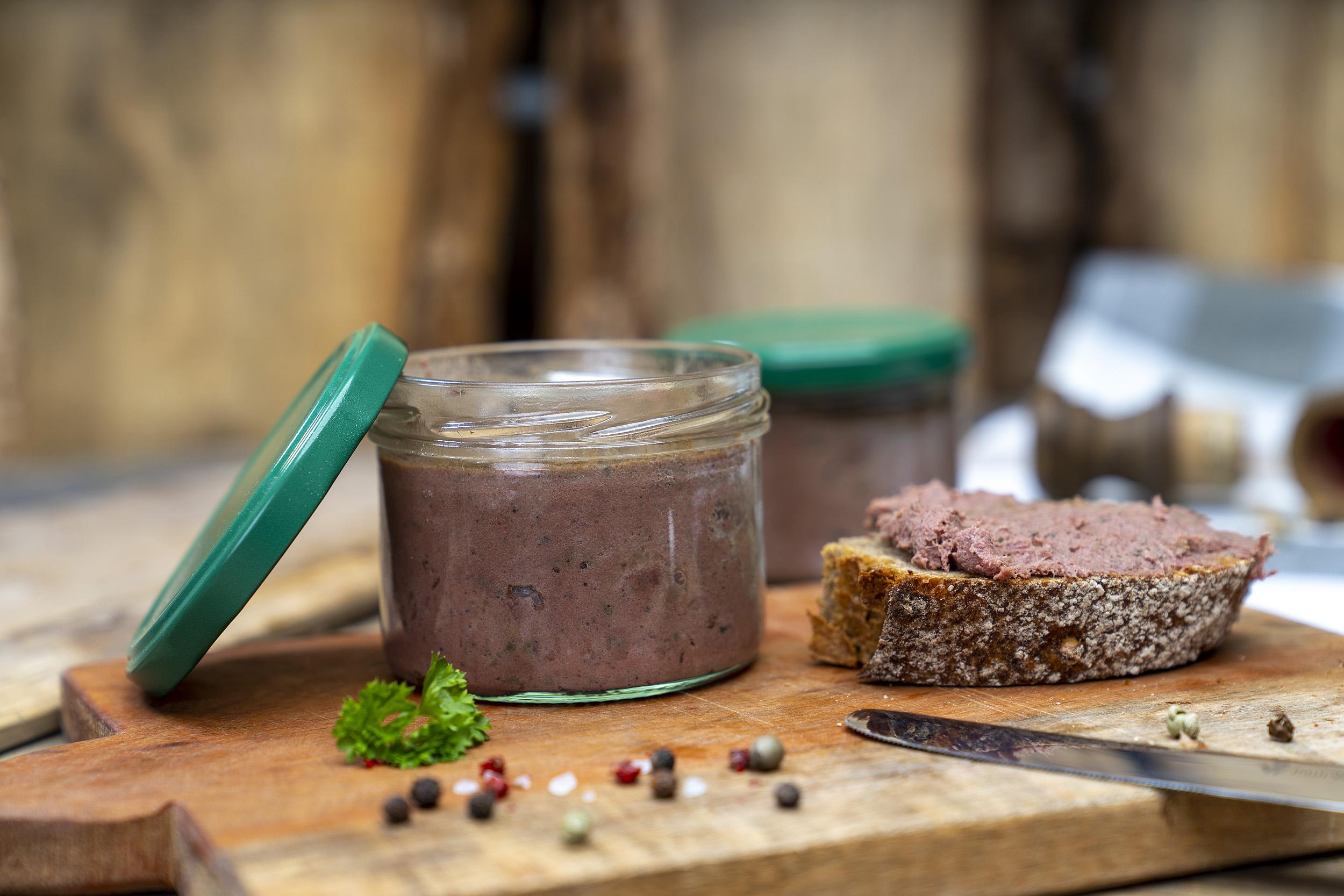 Auf einem Brett ein Glas mit Wildleberwurst. Daneben ein geschmiertes Brot und Gewürze. Im Hintergrund noch ein Glas.