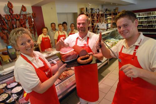 Bettina, Erwin und Hendrik Fessel mit roten Schürzen im Vordergrund. Neueröffnung des Ladens in 2010. Im Hintergrund die Theke und das Team.