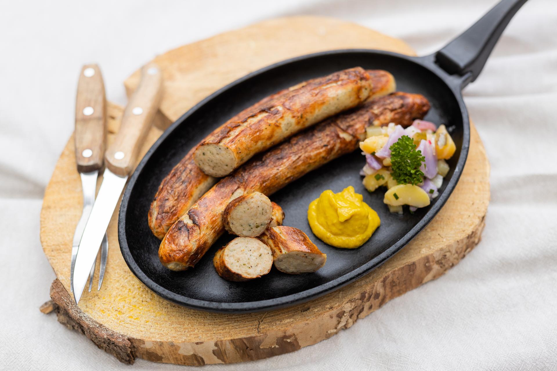 Gebratene Original Thüringer Rostbratwurst in der Pfanne auf einem Brett. In der Pfanne Senf und Salatbeilage. Neben der Pfanne Besteck.