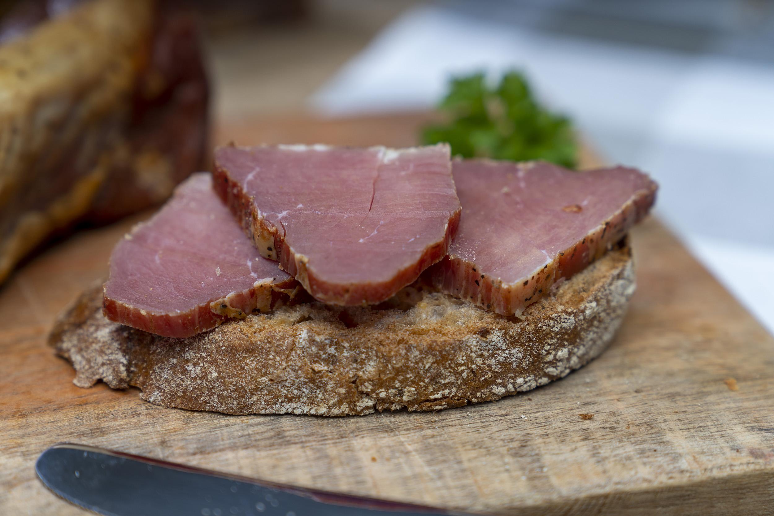 Ein Stück Schinkenfilet der Fleischerei Fessel. Daneben ein Brot mit Schinken.