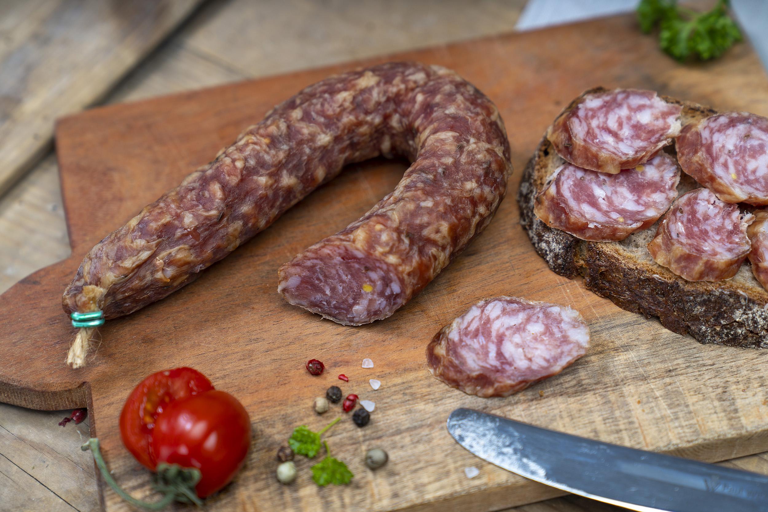 Ein Südharzer Knüppelchen auf einem Brett. Daneben ein Brot mit der Wurst, Gewürze und eine Tomate.