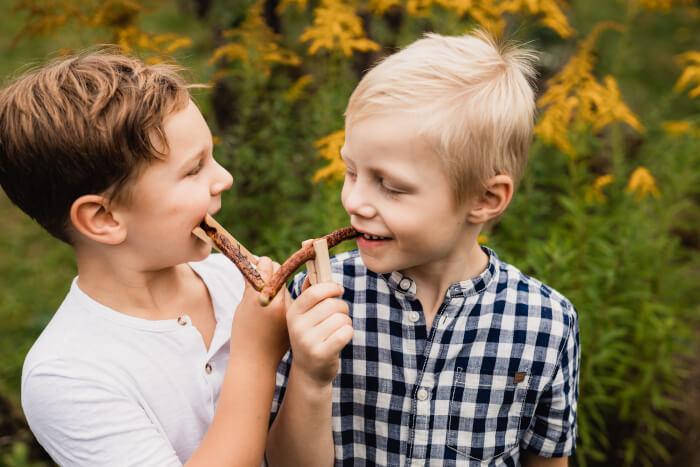 Zwei Jungen nebeneinander. In der Hand haben beide eine Klammerwurst an der Holzklammer.
