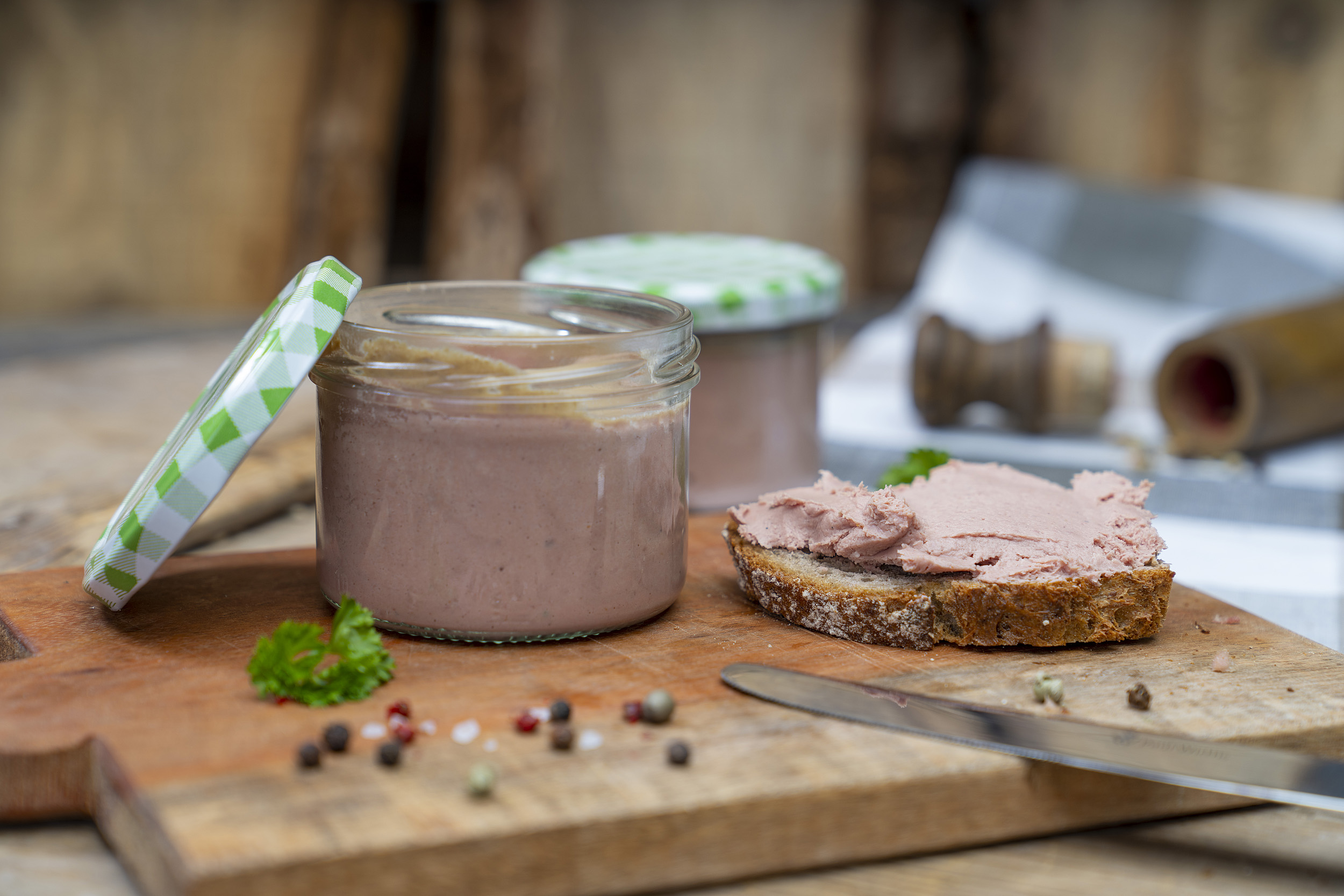 Auf einem Holzbrett ein Glas mit Kalbfleischleberwurst. Daneben eine Schnitte mit Leberwurst beschmiert und Gewürze. Am Brett vorn liegt ein Messer. Im Hintergrund ein weiteres Glas.