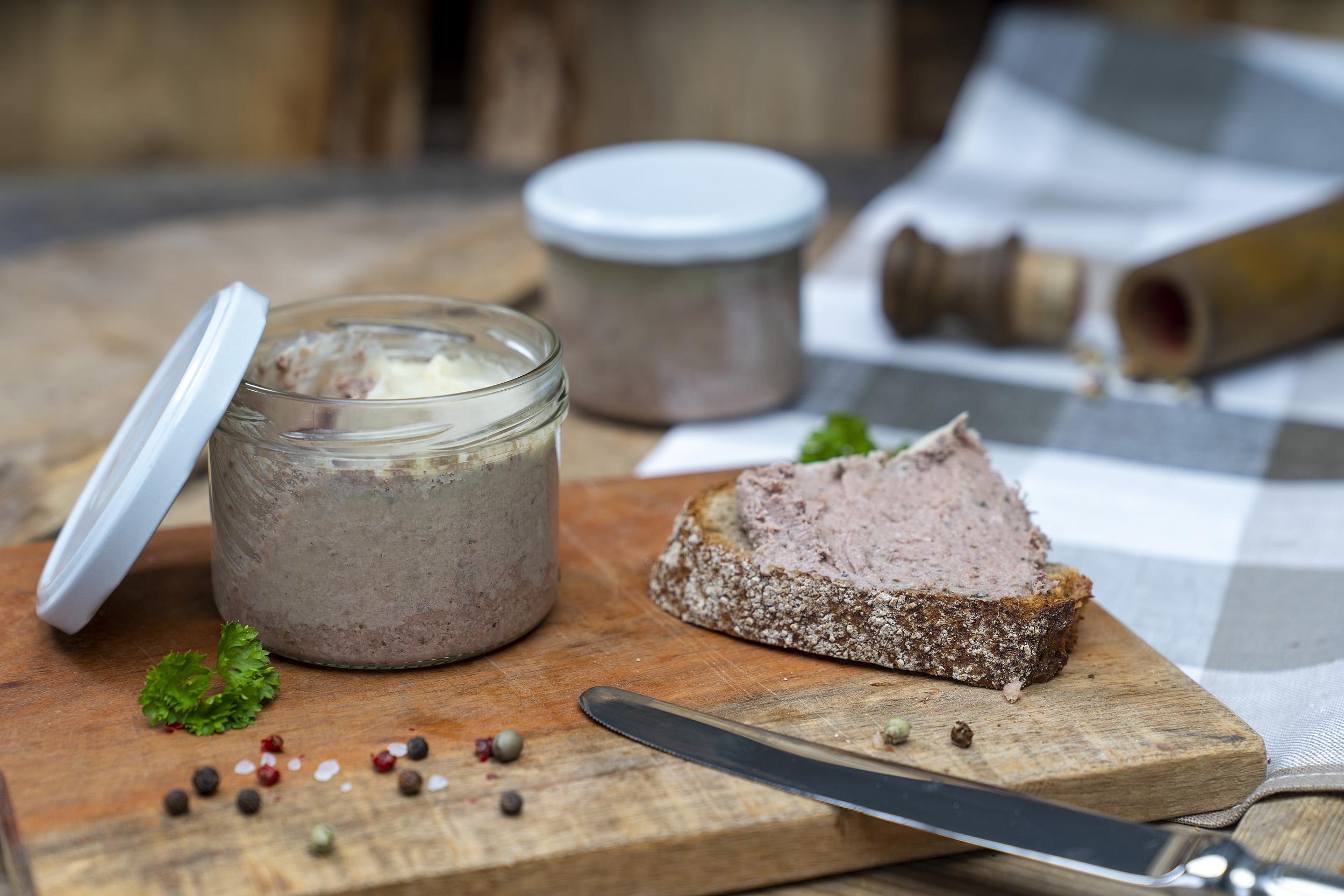 Auf einem Holzbrett ein Glas mit Hausmacher Leberwurst. Daneben eine geschmierte Schnitte, Kräuter und Gewürze. Am Brett ein Messer und im Hintergrund ein weiteres Glas.