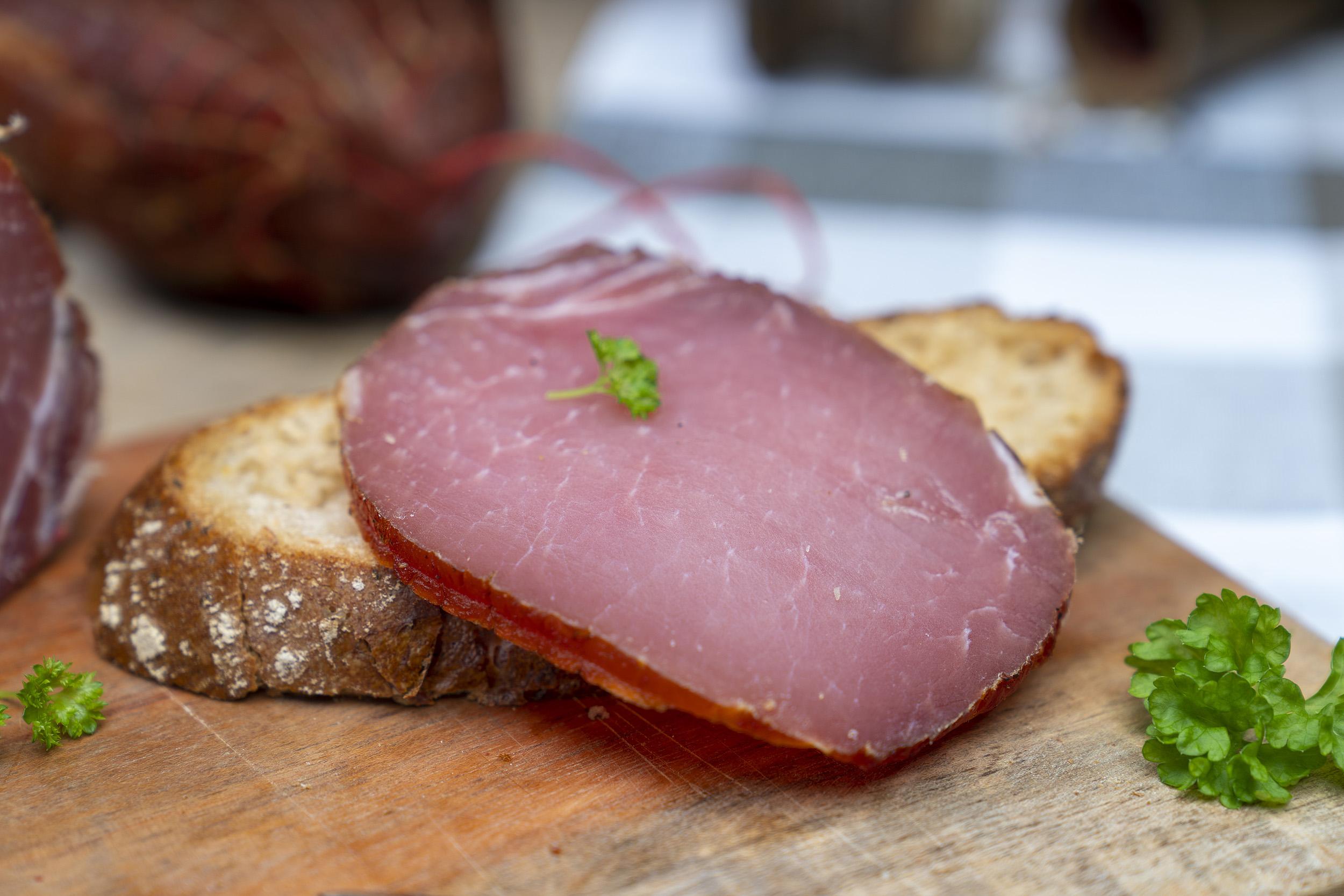 Auf einem Brot eine Scheibe Lachsschinken. Daneben Petersilie und der Schinken.