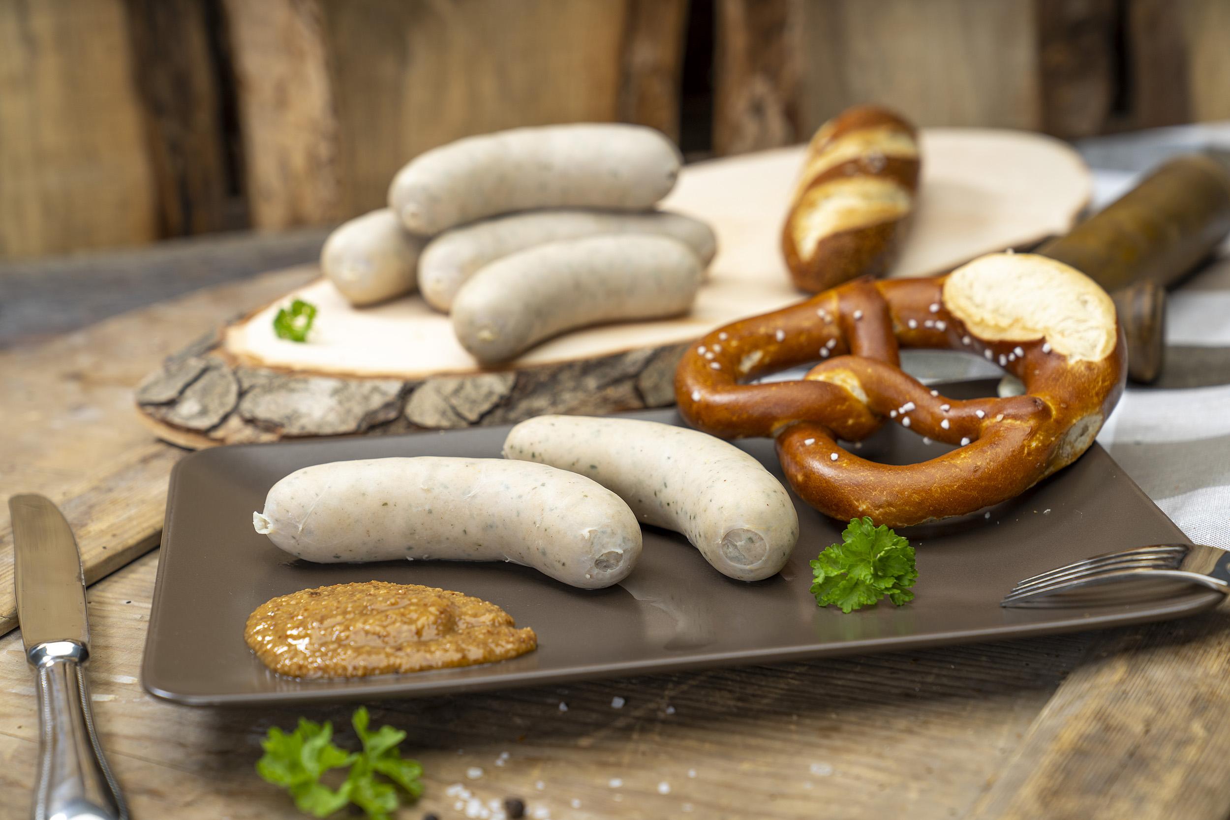 Zwei Weißwürste, eine Brezel und süßer Senf auf einem Teller. Im Hintergrund weitere Würste der Fleischerei Fessel.