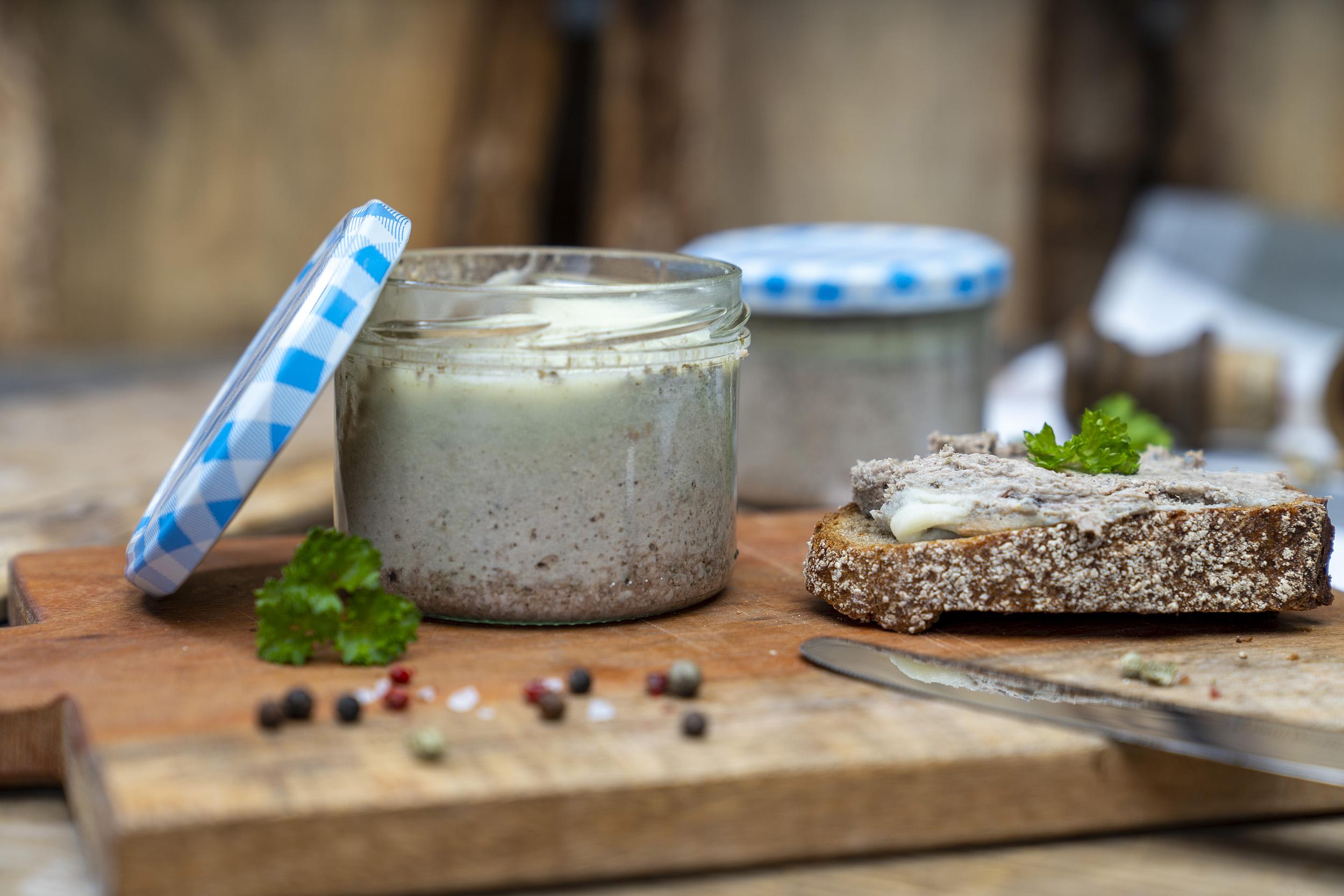 Ein Glas Zwiebelleberwurst auf eine Brett. Ein beschmiertes Brot und Gewürze daneben. Hinten ein weiteres Glas der Leberwurst.