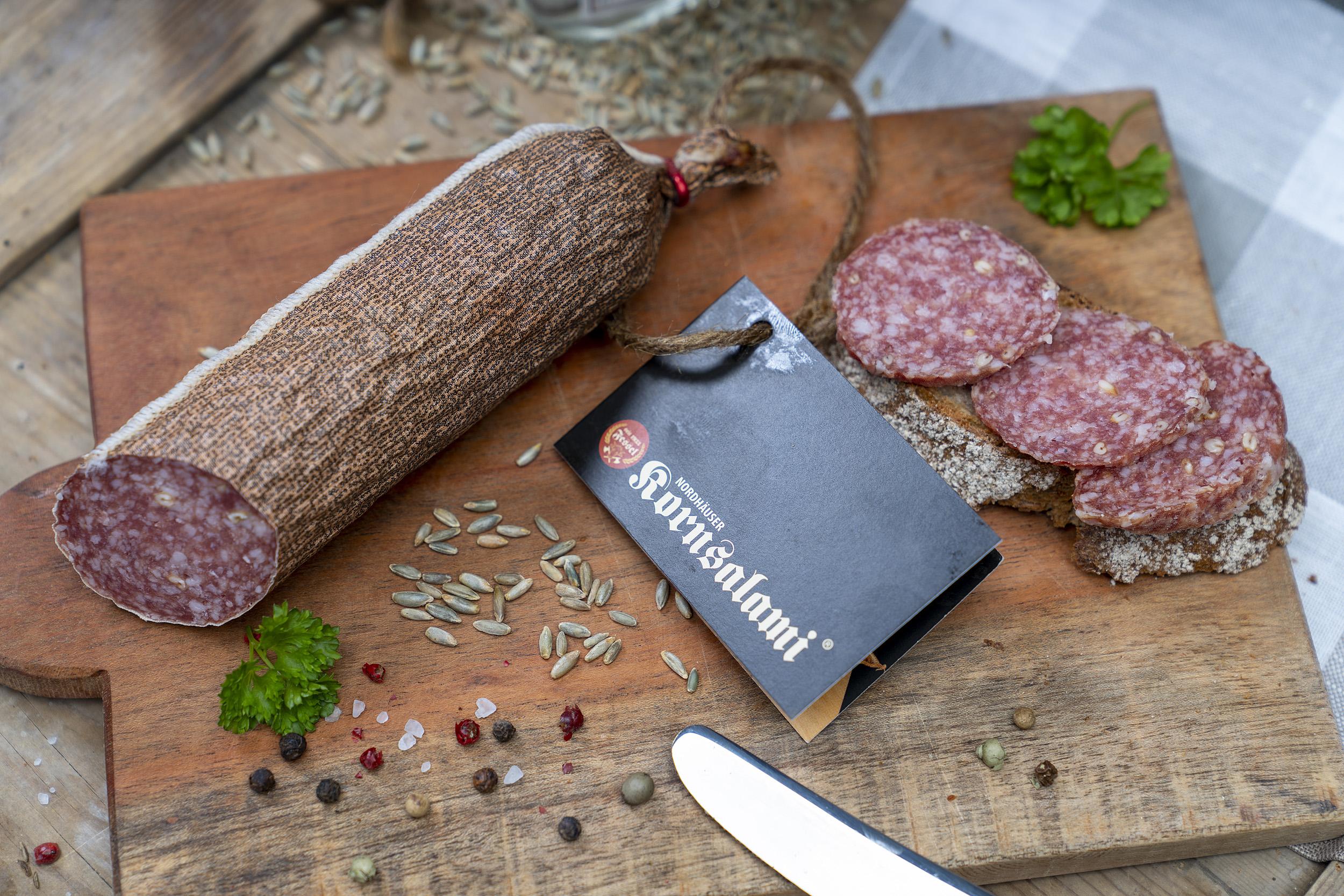 Kornsalami auf einem Holzbrett. Daneben eine Scheibe Brot mit der Salami und Gewürze.