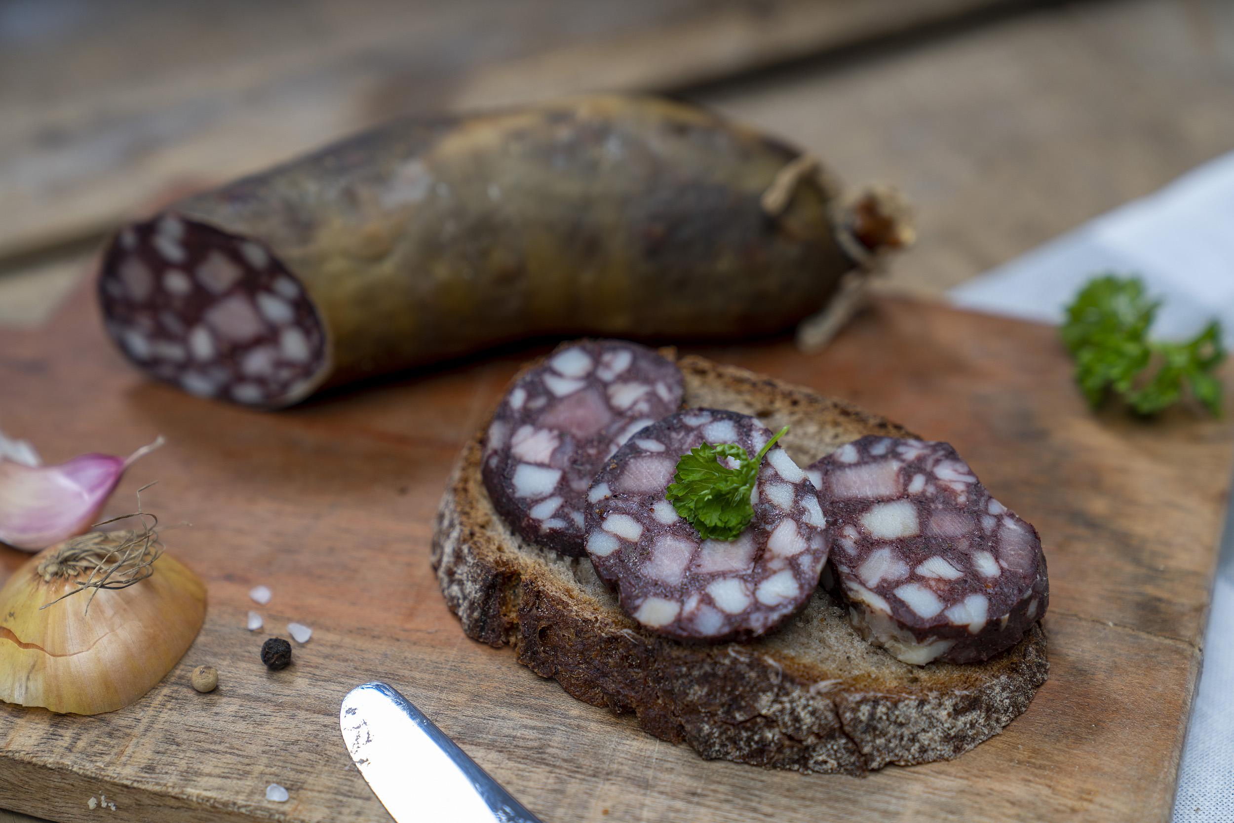 Eine Scheibe Brot mit Rotwurst Scheiben. Auf dem Brett Kräuter, Zwiebeln und die Wurst.