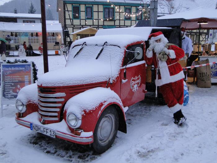 Der neue Framo ganz in rot. Er steht auf dem Weihnachtsmarkt in Ilfeld und ist ganz zu geschneit. Daran lehnt der Weihnachtsmann. Im Hintergrund Lichter und Häuser.