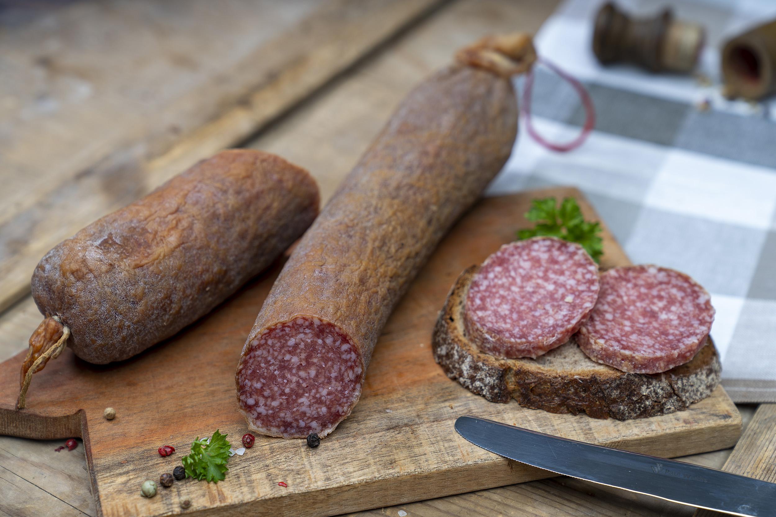 Aufgeschnittene Schlackwurst auf einem Brett. Daneben ein Brot mit der Wurst.