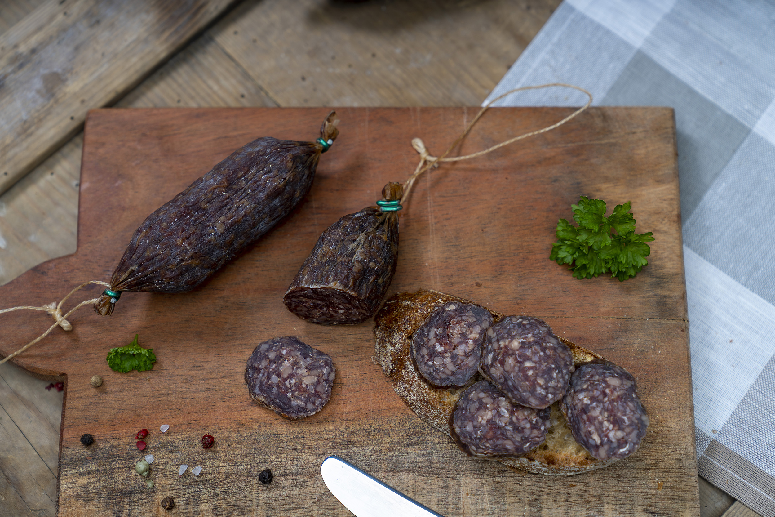 Einige Rindsalamis auf einem Holzbrett. Daneben eine Schnitte mit der Salami.