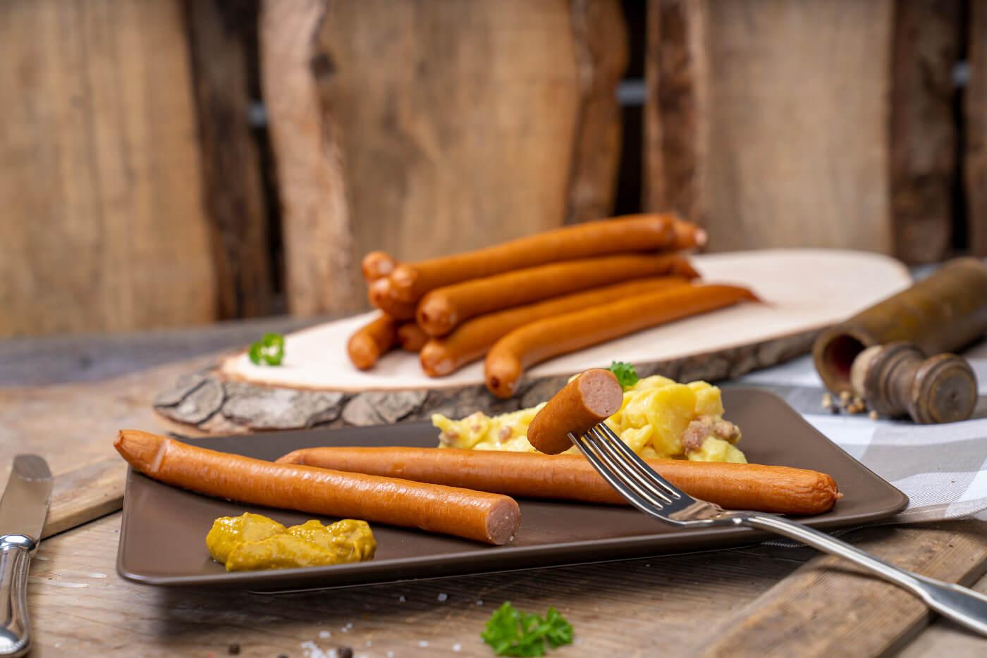 Zwei Wienerwürstchen, Kartoffelsalat und Senf. Hinten weitere Wiener der Fleischerei Fessel.