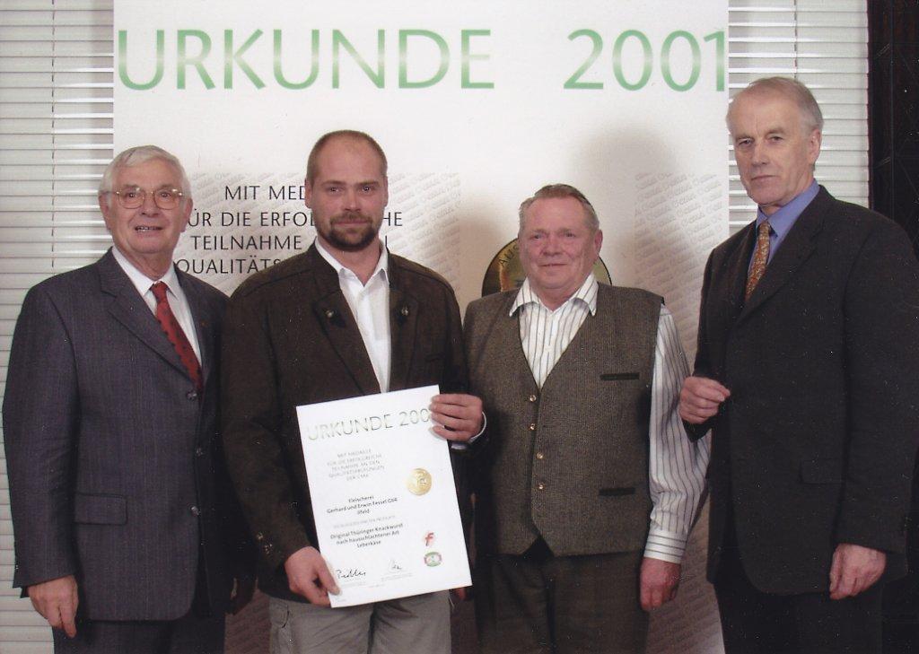 Erwin und Gerhard Fessel bekommen eine Urkunde. Sie stehen vor einem Aufsteller mit dem Titel Urkunde 2001.