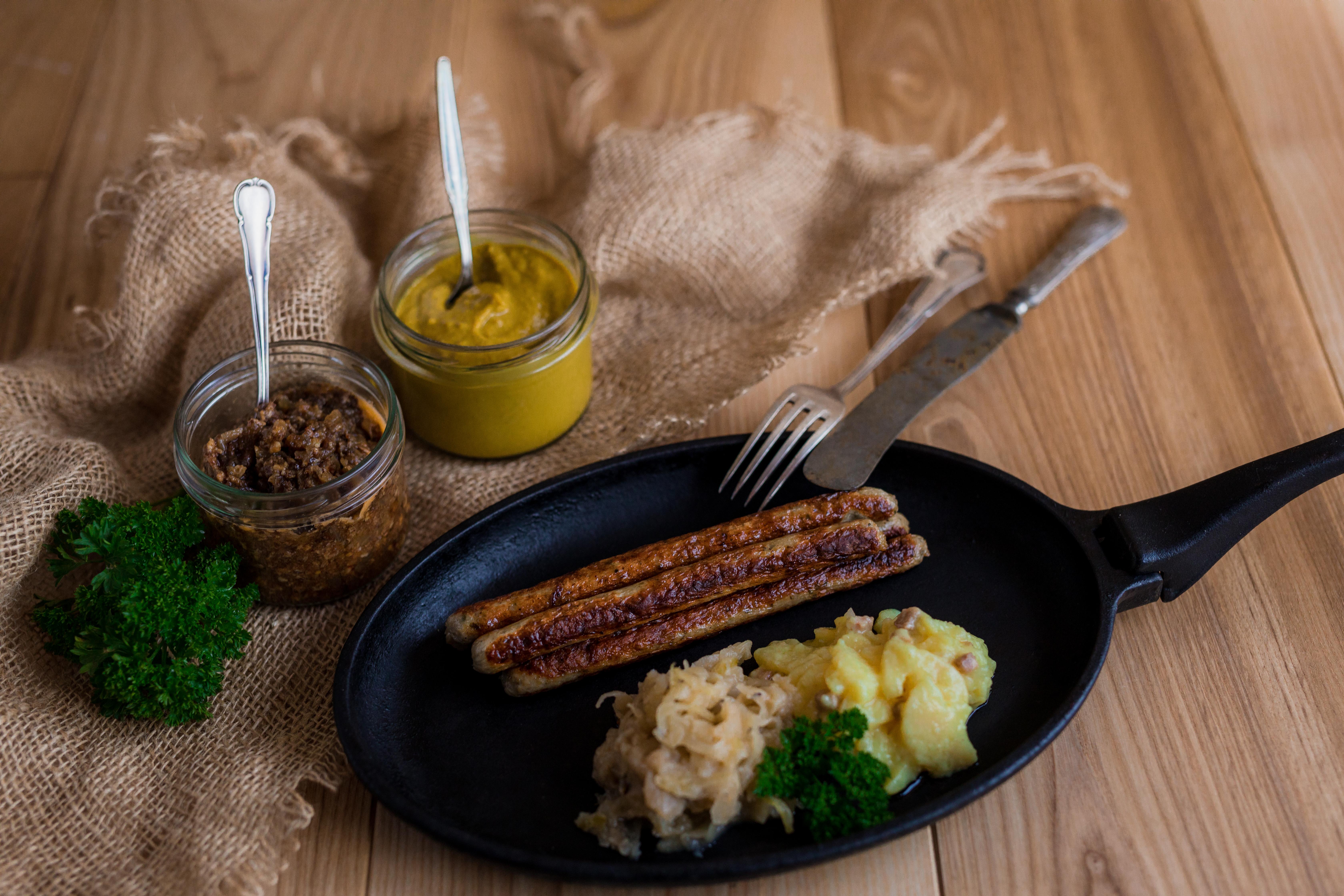 Gebratene Klammerwürste in einer Pfanne mit Sauerkraut und Salatbeilage. Neben der Pfanne Gläser mit Saucen. Untergrund aus Holz.