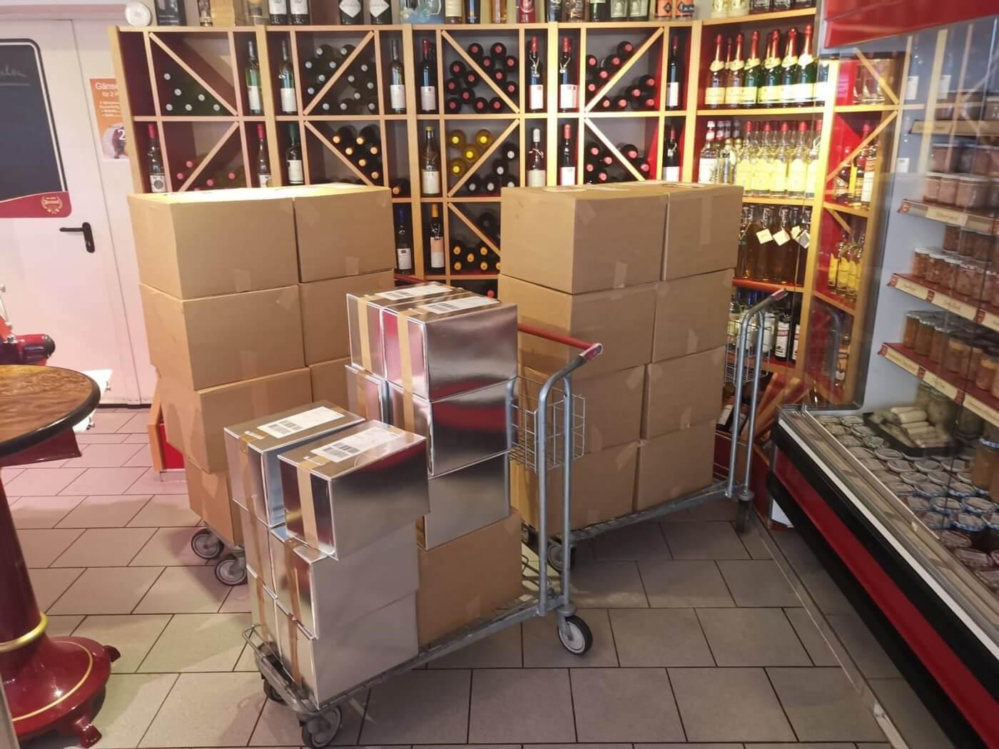 Viele verpackte Onlinebestellungen im Laden der Fleischerei. Im Hintergrund ein Weinregal und Konserven.