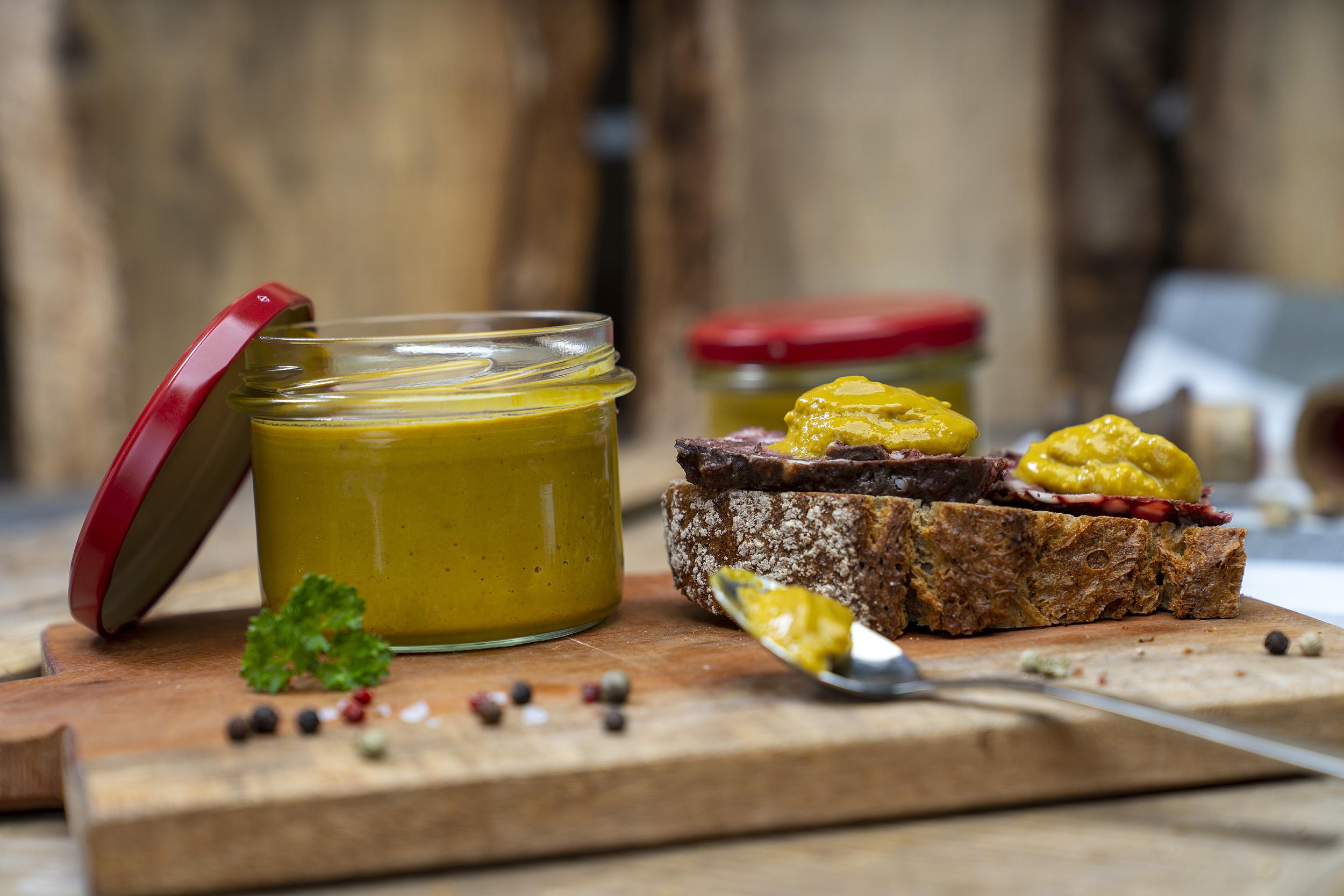 Auf einem Holzbrett ein Glas Senf bzw. Meisters Mostrich. Daneben eine Schnitte mit Rotwurst und Senf. Darum Gewürze und Kräuter. Vorn ein Löffel mit etwas Senf. Hinten ein weiteres Glas.