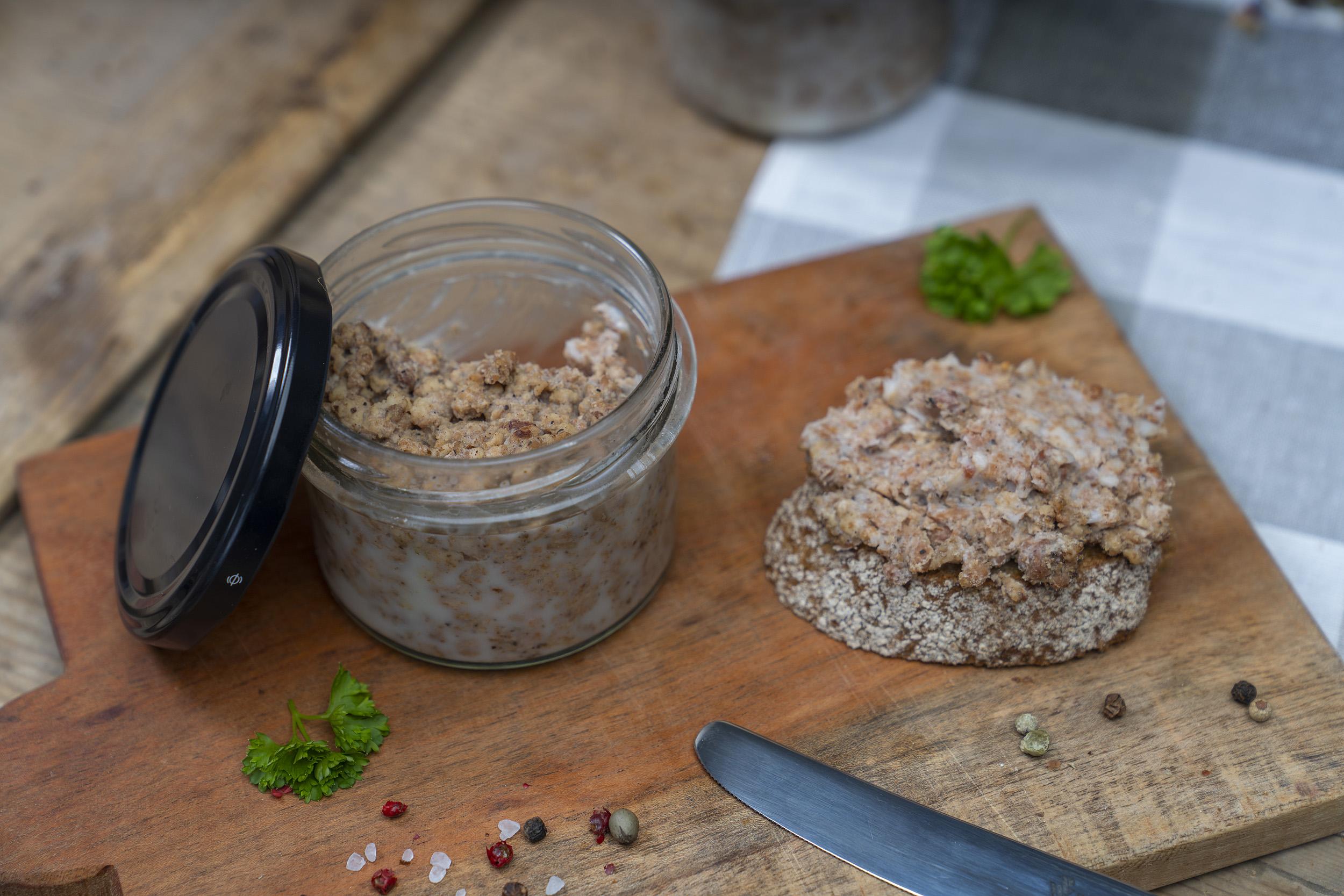 Auf einem Holzbrett ein Glas Pott Suse, also geschmortes Hackfleisch. Daneben eine Scheibe Brot mit Pott Suse und Gewürze.