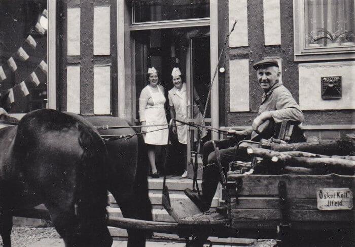 Außenansicht des alten Ladens. Vorn eine Pferdekutsche und einem Mann. Im Hintergrund Annaliese Fessel und eine andere Frau in weißem Kittel. Sie schauen aus der Tür des Fachwerkhauses.