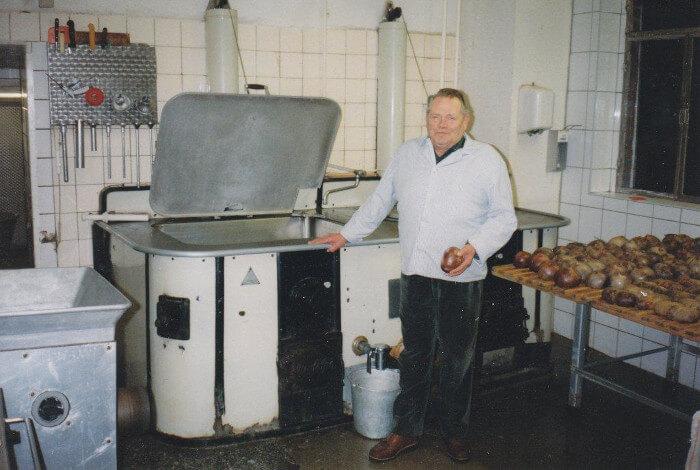 Gerhard Fessel in der Fleischerei. Neben ihm viele Produkte.