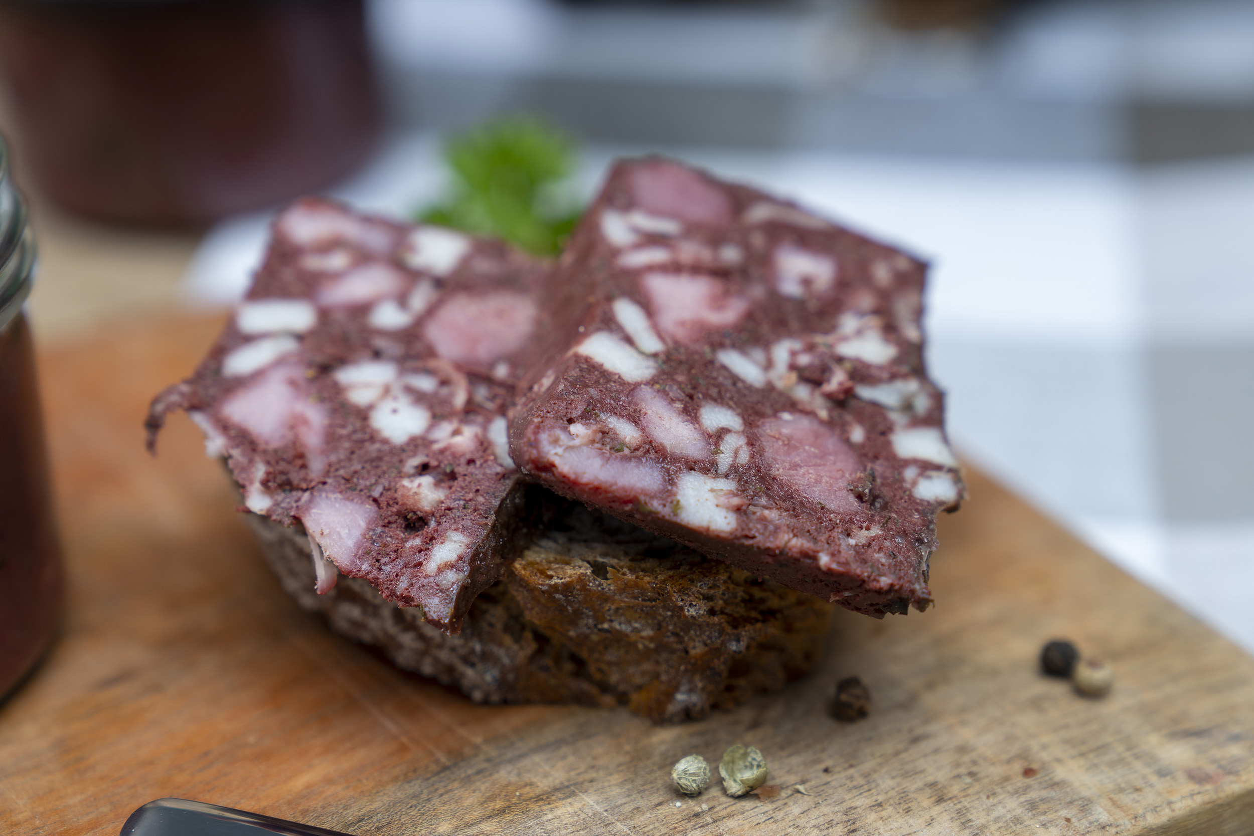 Auf einem Holzbrett steht ein Glas Rotwurst. Daneben eine Scheibe Brot mit Rotwurst Scheiben. Darum Gewürze. Hinten ein weiteres Glas Rotwurst.