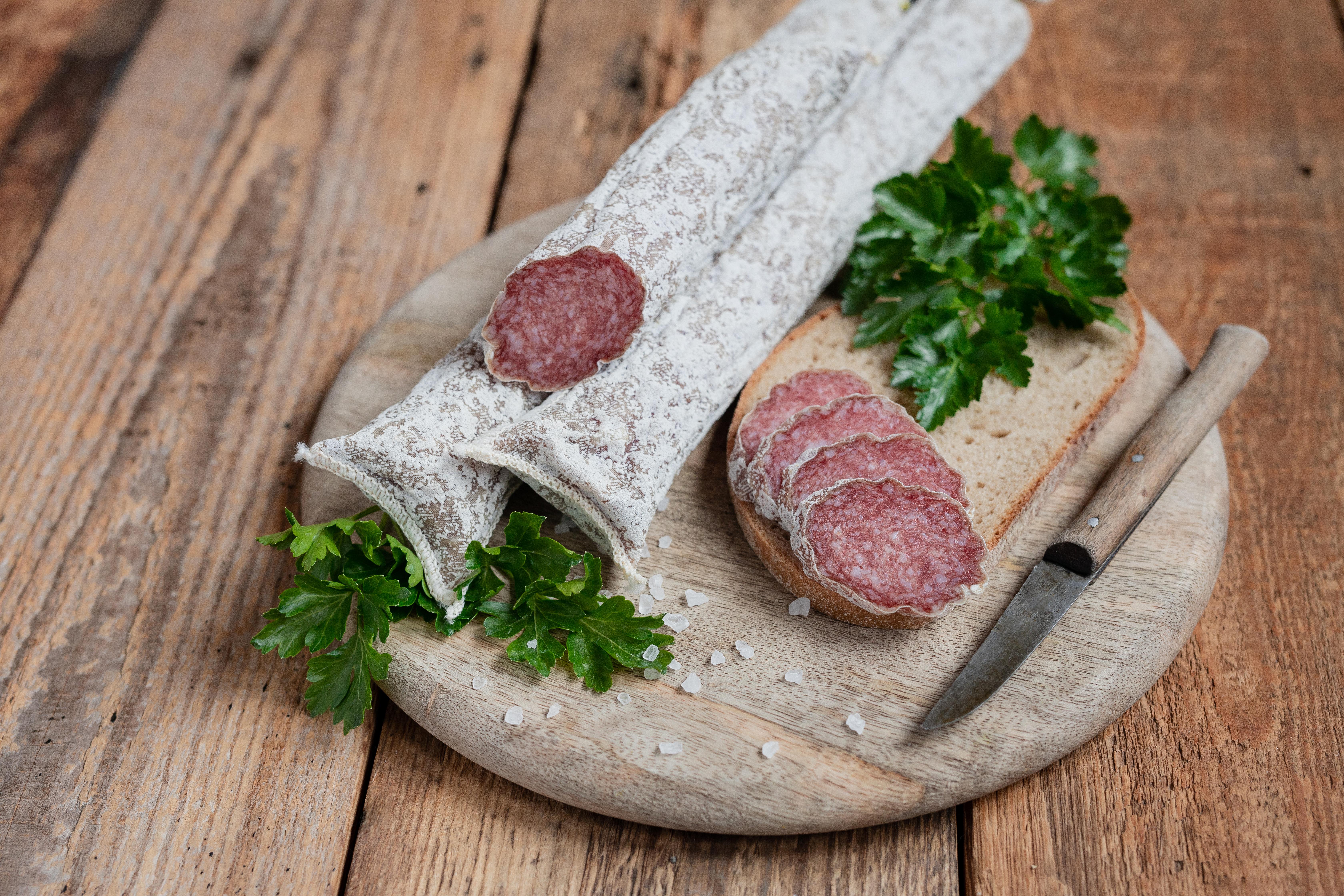 Auf einem Brett zwei mediterrane Salami. Daneben drei Scheiben der Salami, Kräuter und ein Messer.