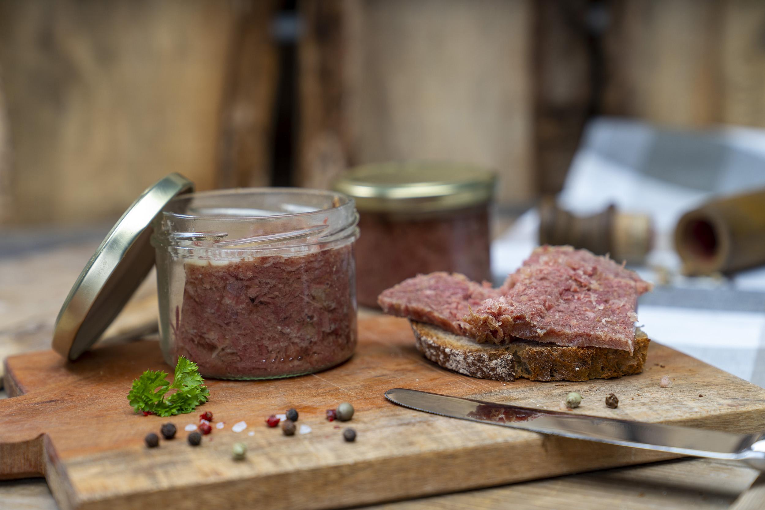 Auf einem Brett ein Glas Corned beef. Daneben ein geschmiertes Brot mit Corned beef. Daneben Gewürze, Kräuter und ein Messer. Im Hintergrund ein weiteres Glas.