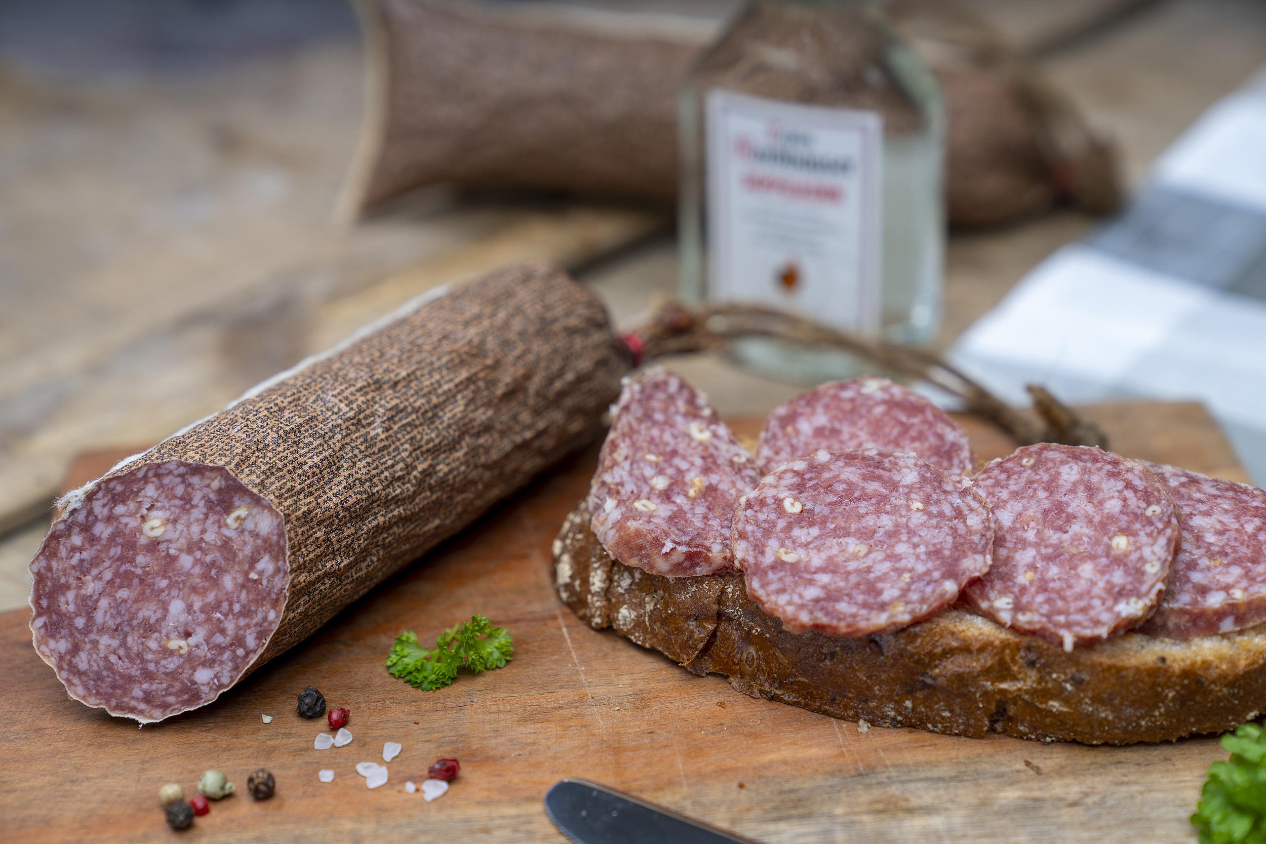 Kornsalami auf einem Holzbrett. Daneben eine Scheibe Brot mit der Salami und Gewürze. Im Hintergrund eine kleine Flasche Echter Nordhäuser Doppelkorn.