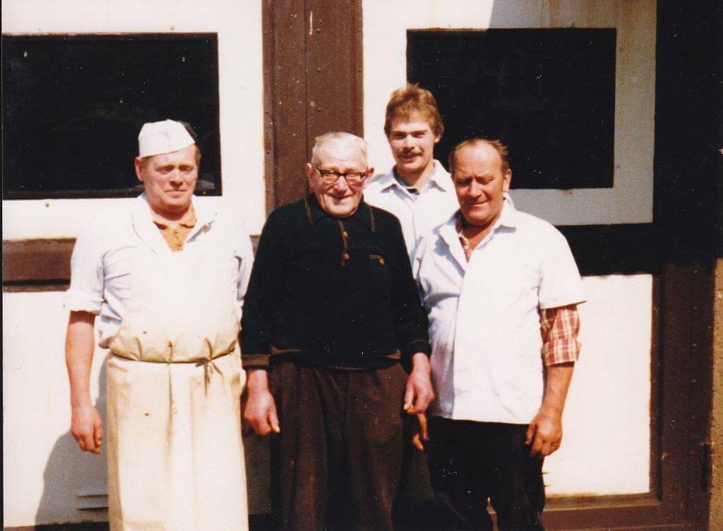 Gerhard, Karl und Erwin Fessel stehen vor der Fleischerei.