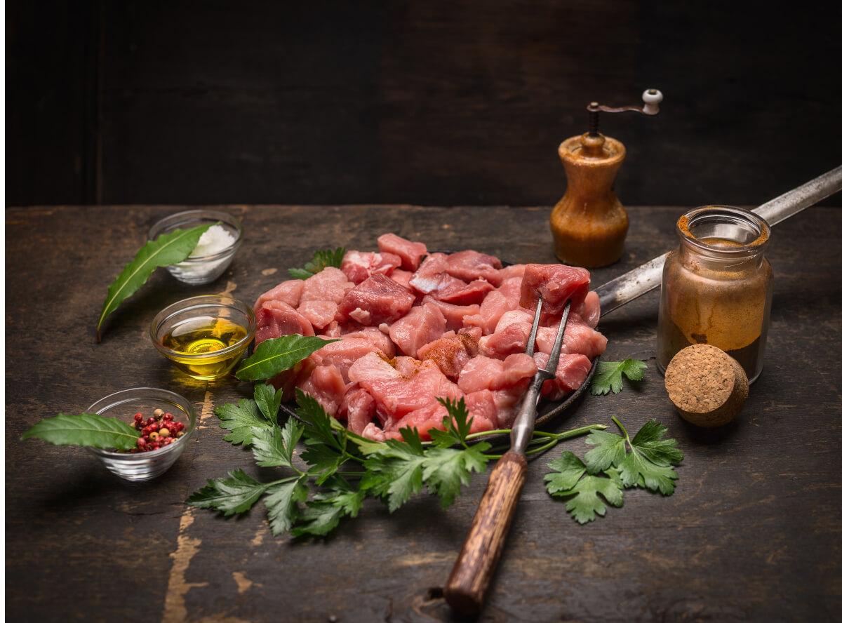 Auf einem Holz rohe Schweinegulaschwürfel. Daneben Gewürze und Kräuter.