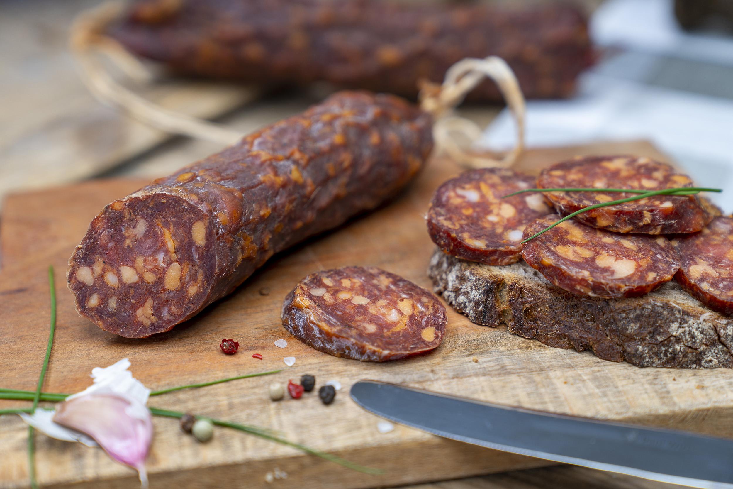 Angeschnittene Ungarische Salami auf einem Brett. Daneben eine Schnitte mit der Wurst und Gewürze. Im Hintergrund eine weitere Salami.