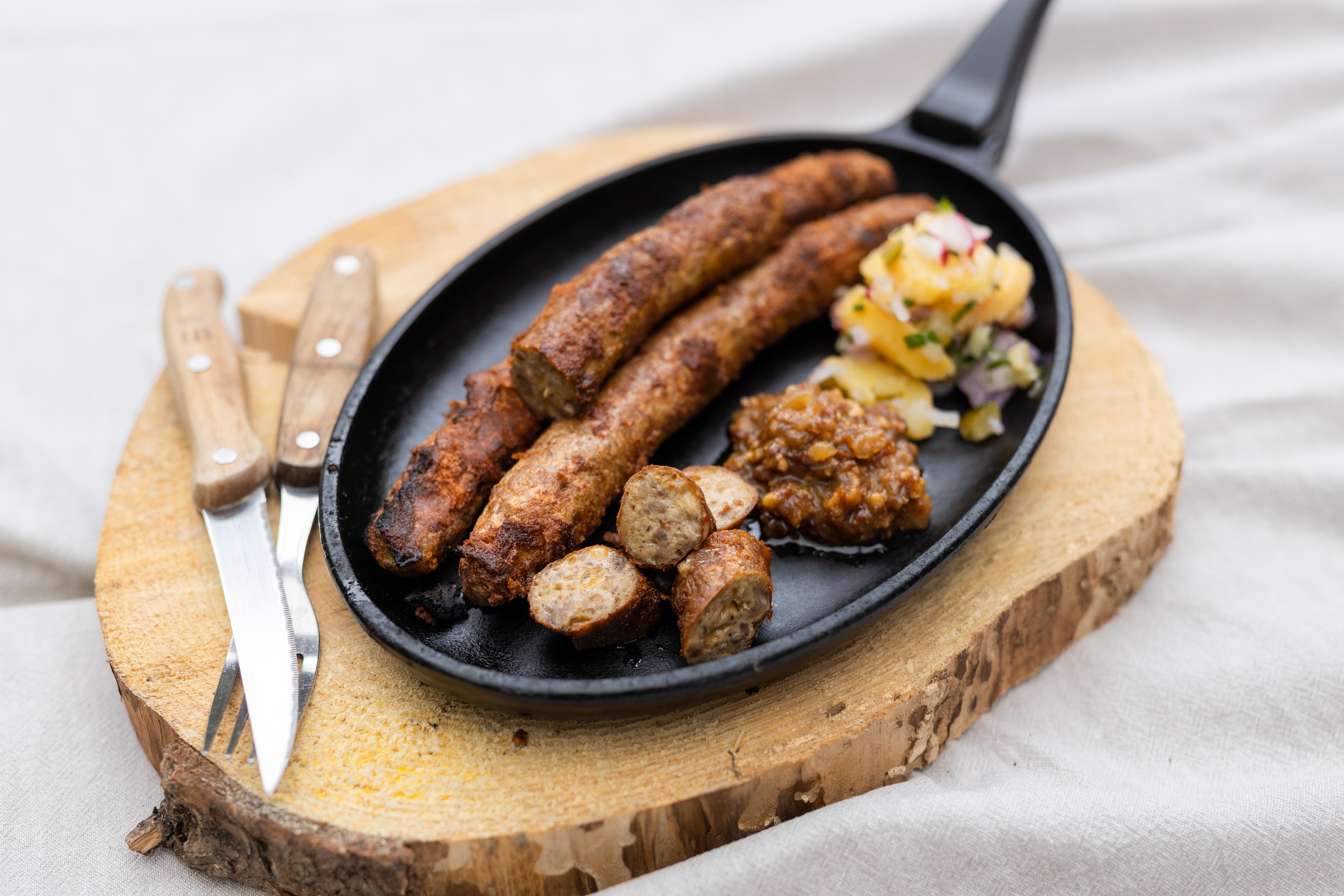 Drei Cheesburger Bratwürste in einer Pfanne. Einige Stücke sind abgeschnitten. Daneben Saucen und Salatbeilage. Unter der Pfanne ein Brett und Besteck daneben.