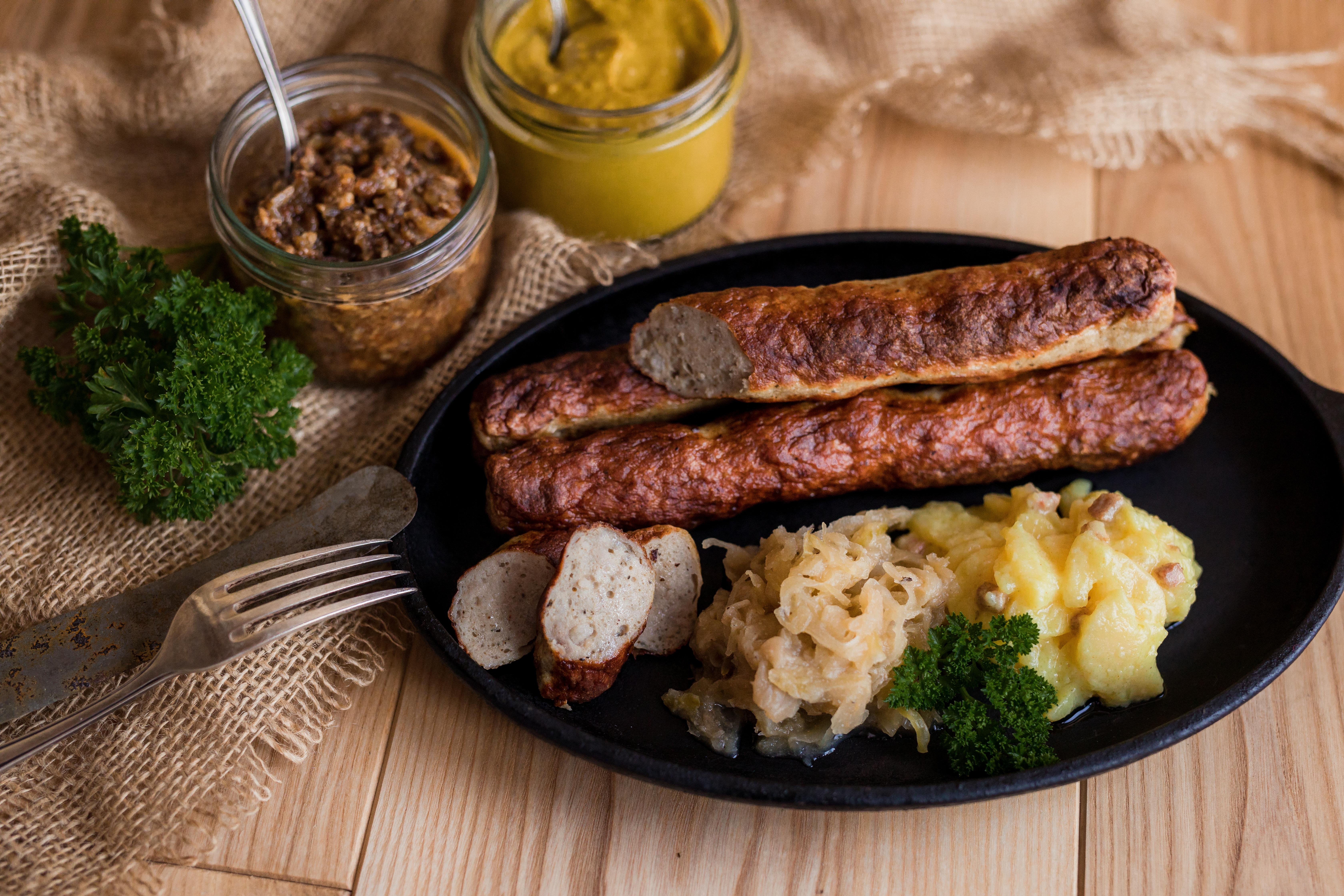 Gebratene Grillies in der Pfanne. Ein paar Stücke sind aufgeschnitten und Sauerkraut und Salatbeilage sind daneben. Neben der Pfanne Saucen-Gläser und Kräuter auf Holz-Untergrund.