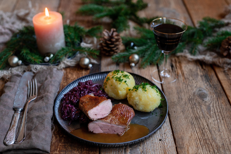 Gänsebrust, Rotkohl und Klöße auf einem Tisch. Daneben Besteck, ein Glas Rotwein und Deko.