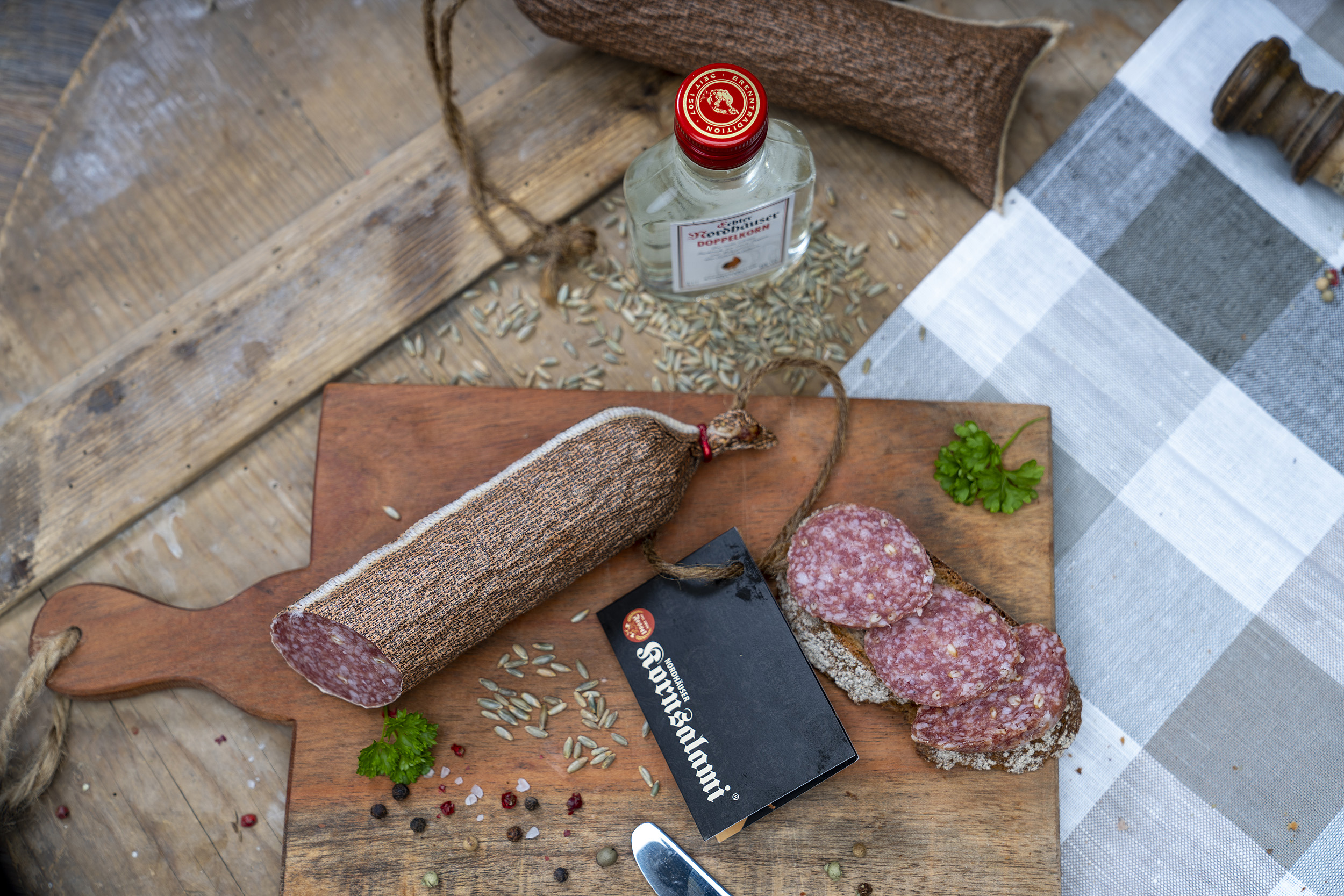 Kornsalami auf einem Holzbrett. Daneben eine Scheibe Brot mit der Salami und Gewürze. Neben dem Brett eine kleine Flasche Echter Nordhäuser Doppelkorn.