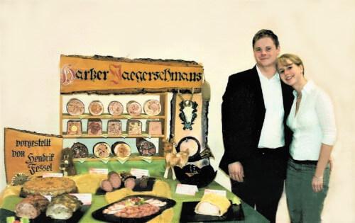 Hendrik und Olga Fessel vor seinem Meisterstück. Auf einem Tisch liegen viele Fleischspezialitäten unter der Überschrift Harzer Jaegerschmaus.