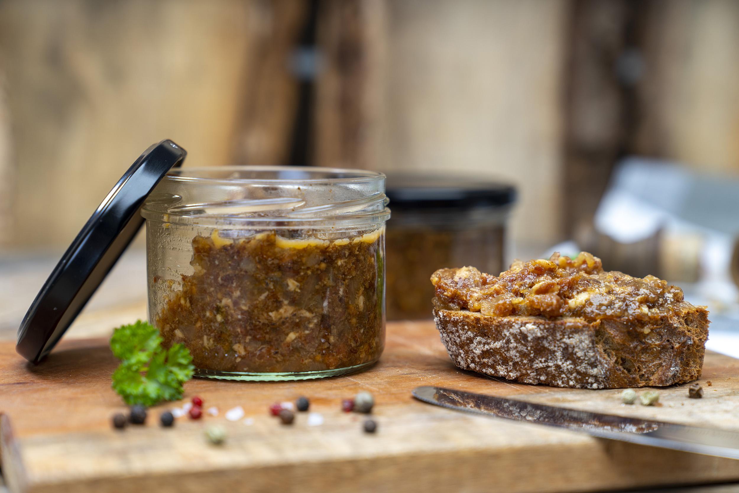 Auf einem Holzbrett steht ein Glas mit Bacon Jam. Daneben Gewürze, Kräuter und ein geschmiertes Brot mit der Marmelade. Im Hintergrund ein weiteres Glas. Vorn ein Messer am Brett.